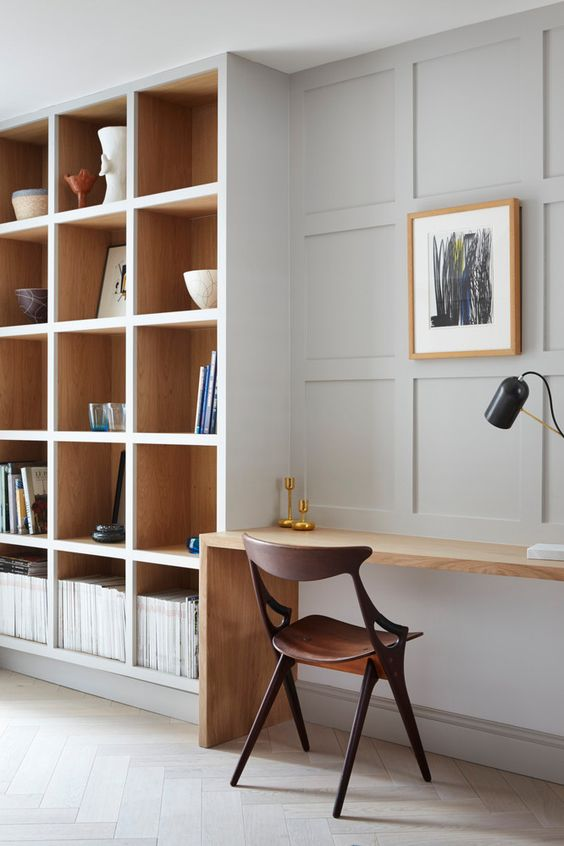 a beautiful minimalist home office with built-in bookshelves and a small built-in desk is a stylish space