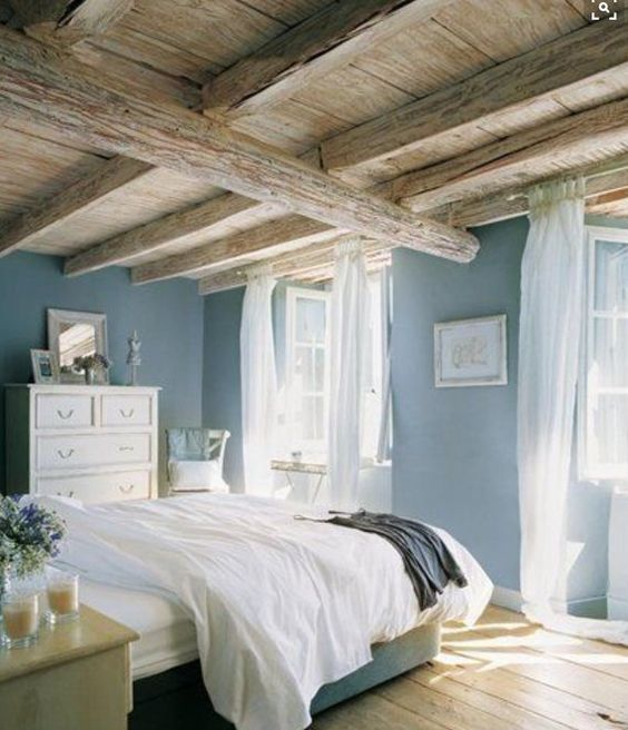 a blue bedroom with wooden beams on the ceiling, neutral furniture, artworks and some blooms