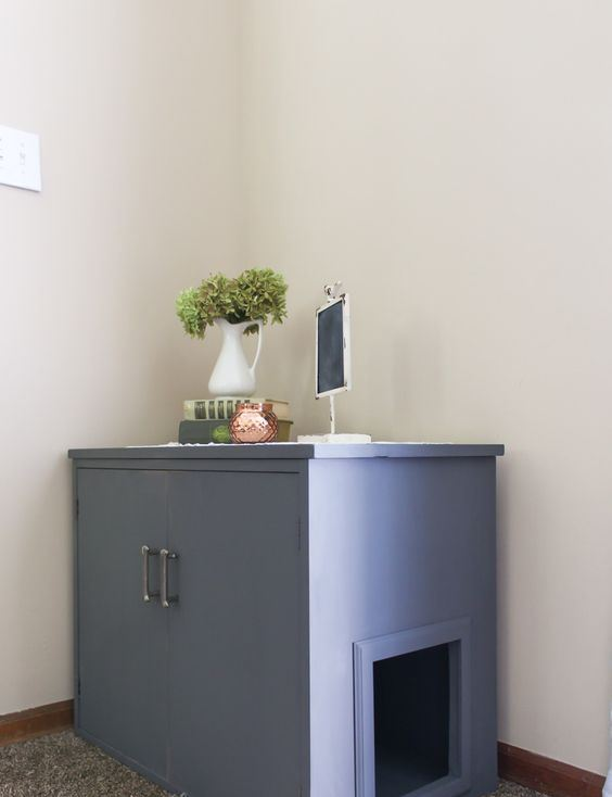 a blue cabinet renovated for a cat, with an entrance and doors for comfortable cleaning can double as a side table