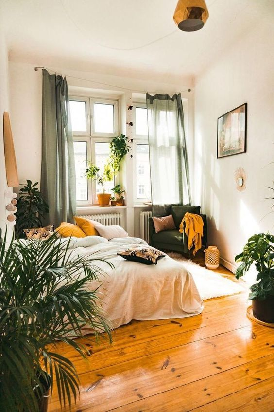 a boho bedroom with green and mustard textiles, candle lanterns, potted plants and catchy lamps