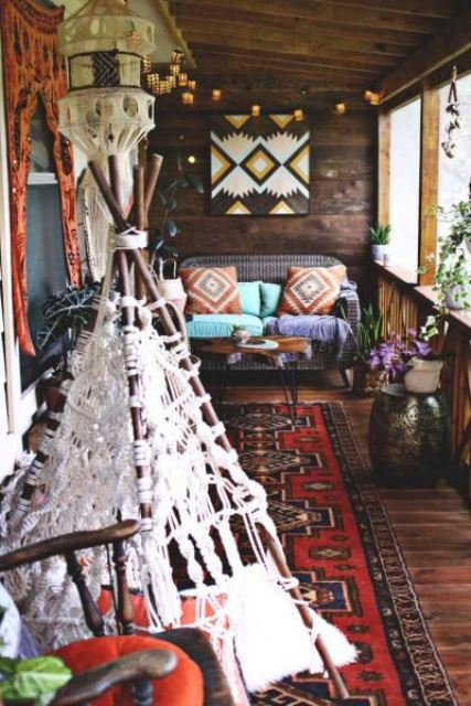 a boho porch with woven and wooden furniture, a boho rug, colorful printed textiles and a macrame teepee