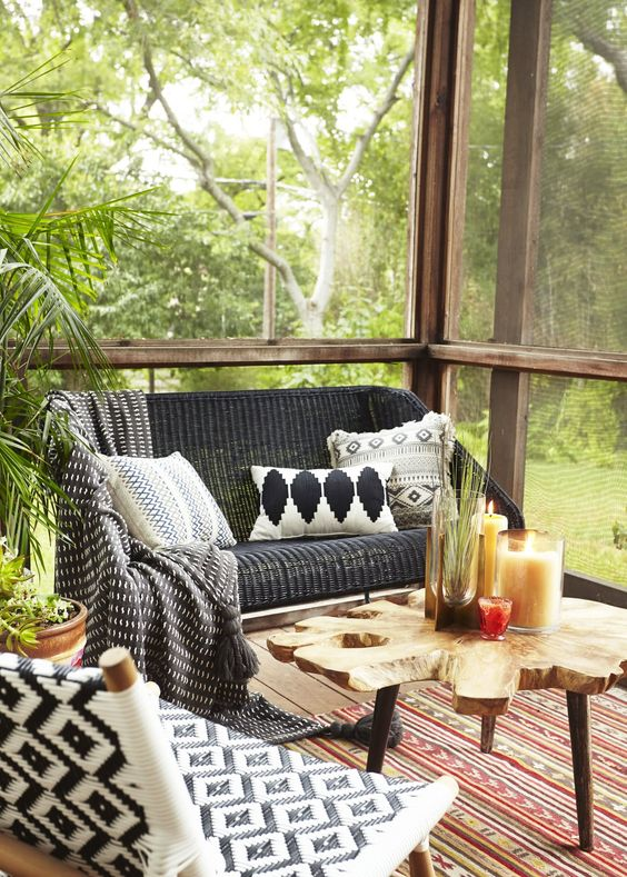 a boho screened porch with woven and wooden furniture, printed textiles, a wood slice rug and potted greenery