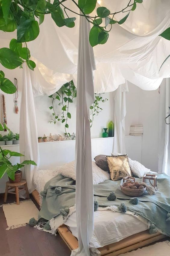 a boho spring bedroom in neutrals with a bed on the floor, pastel bedding, potted greenery