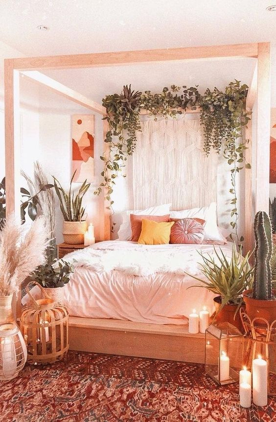 a boho spring bedroom in neutrals, with a wooden canopy bed, potted plants, macrame, candles and a boho rug