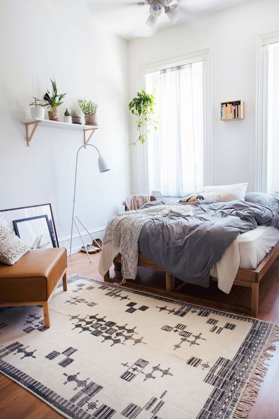 a boho spring bedroom with a wooden bed, a leather chair, blue and white bedding, a printed rug, potted greenery