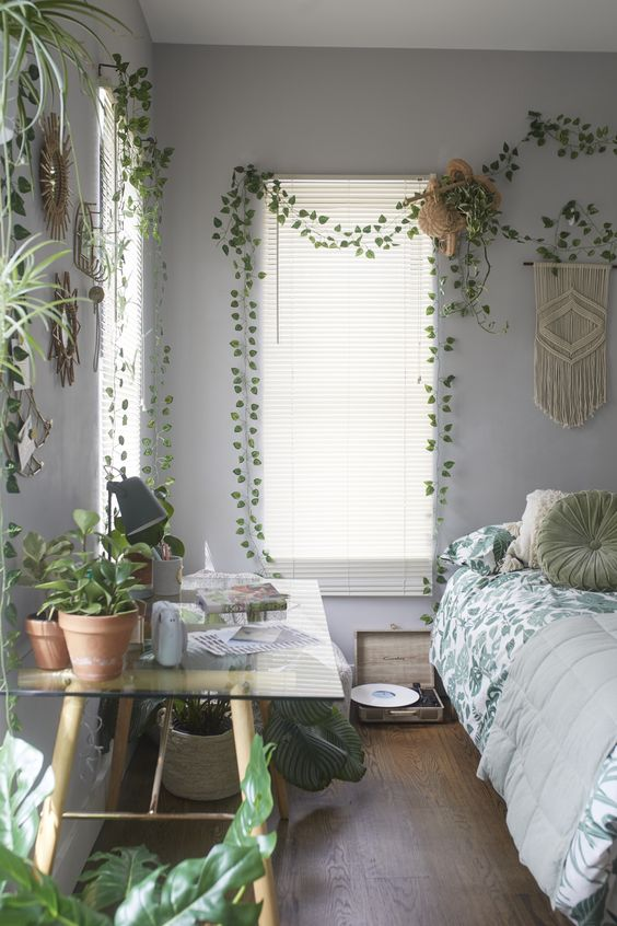 a boho spring bedroom with lots of potted greenery, macrame and botanical bedding