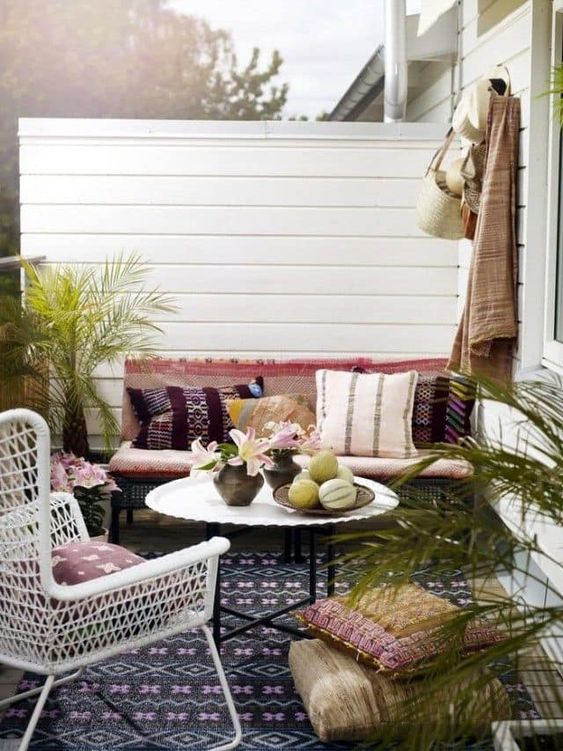 a boho spring terrace with colorful textiles and rugs, potted greenery and a white wicker chair