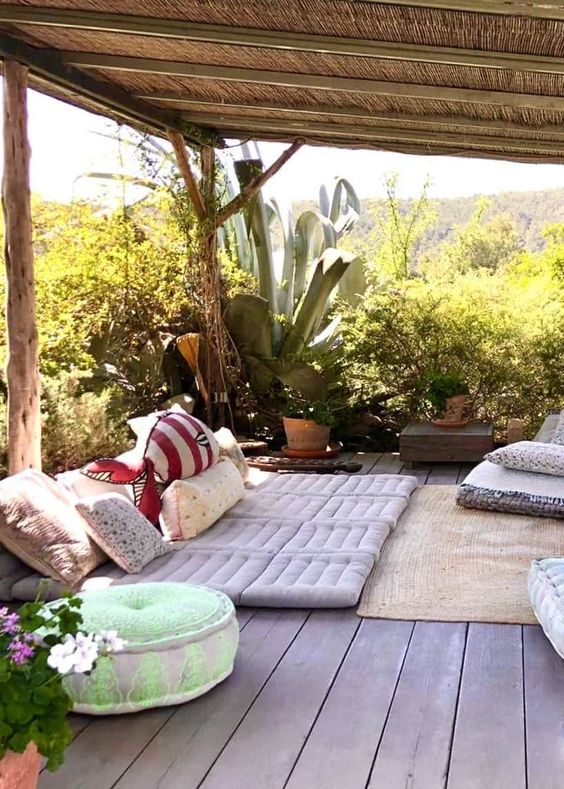 a boho terrace with cushions and pillows, potted greenery and statement plants plus colorful pillows