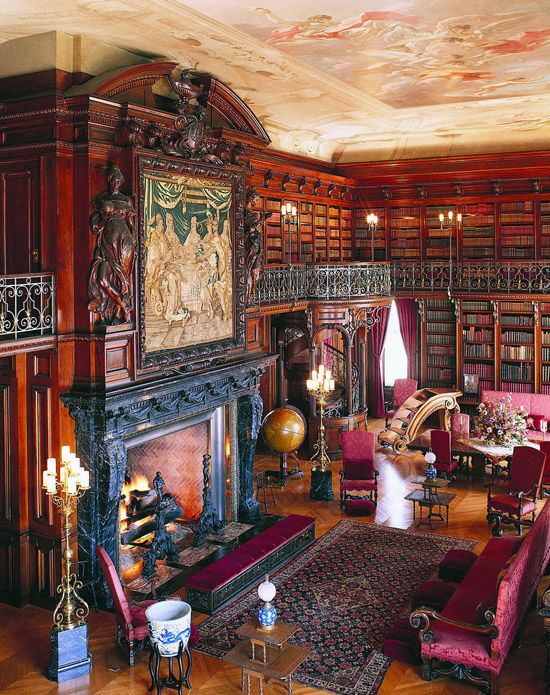 a bold Gothic library in red and fuchsia, with bookcases covering all the walls, a large fireplace and a statement artwork, fuchsia and purple Gothic furniture