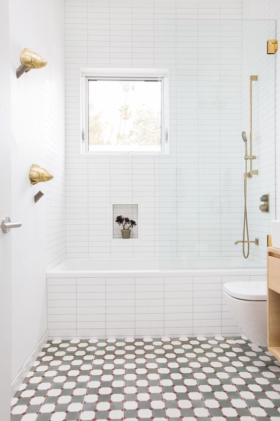 a bright bathroom with a mosaic floor, white tiles with built-in shelves, a window and gold hardware