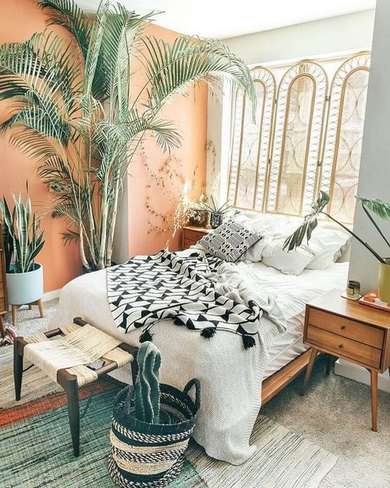 a bright boho bedroom with a rattan screen, wooden furniture, a peachy wall, potted plants and greenery and a wicker stool