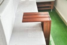 a bright green rug that reminds of grass, green and pink pillows and some flowers for a modern spring balcony
