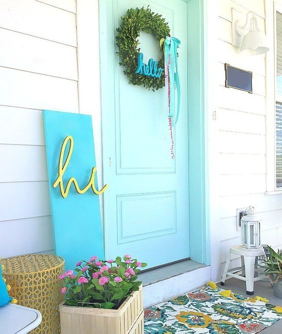 a bright spring porch with a floral mat, potted blooms, a greenery wreath, a modern colorful sign