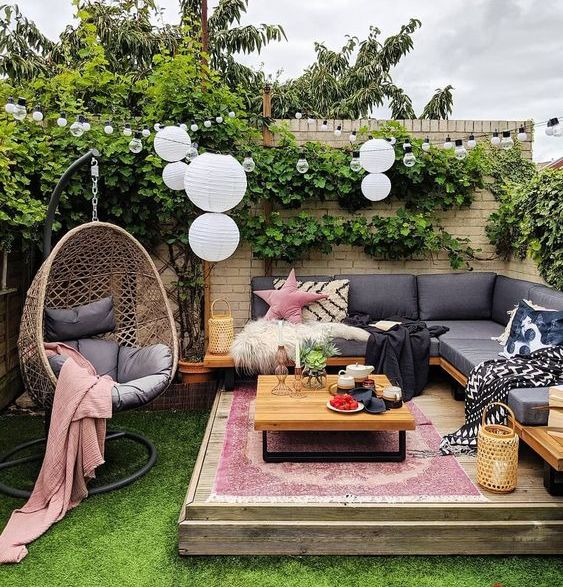 a bright spring terrace with a built-in bench, a table and an egg-shaped suspended chair, boho printed textiles and rugs