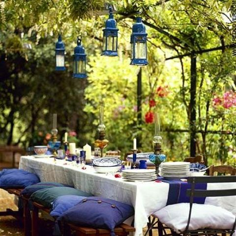 a bright spring terrace with bold linens, blue pillows, blue lanterns over the table and candles and plates