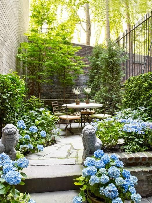 a bright spring terrace with greenery and blue blooms everywhere, with simple modern furniture and potted plants
