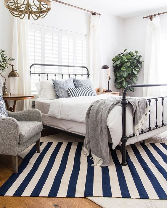 a bright vintage farmhouse bedroom with a metal bed, vintage furniture, grey and blue bedding, potted plants and a beaded chandelier