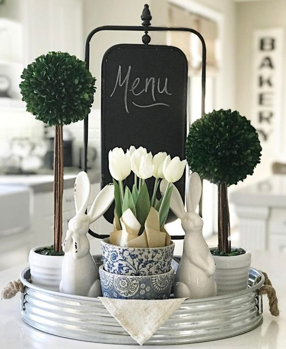 a bucket tray with greenery topiaries, white tulips and bunnies for a farmhouse spring feel in the kitchen
