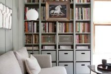 a built-in bookshelf unit with box drawers and a large artwork on it is perfect for a contemporary space