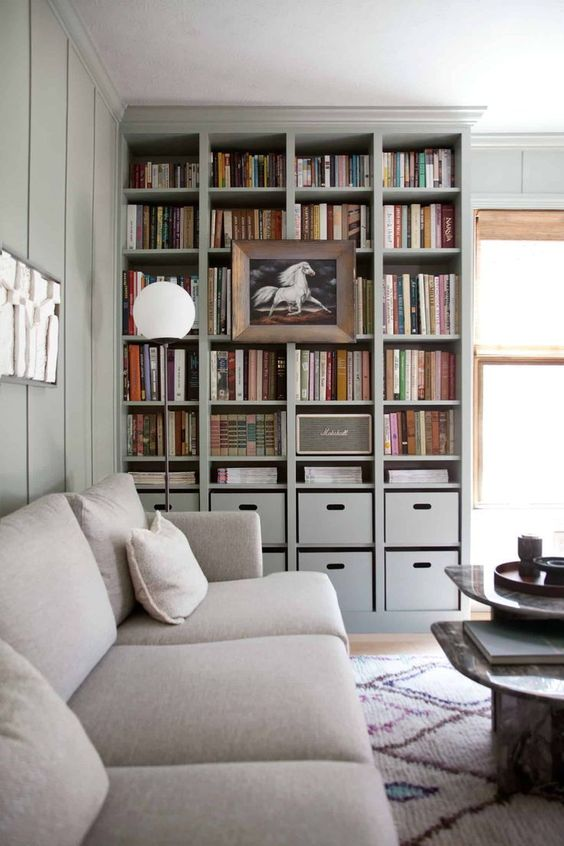 a built in bookshelf unit with box drawers and a large artwork on it is perfect for a contemporary space