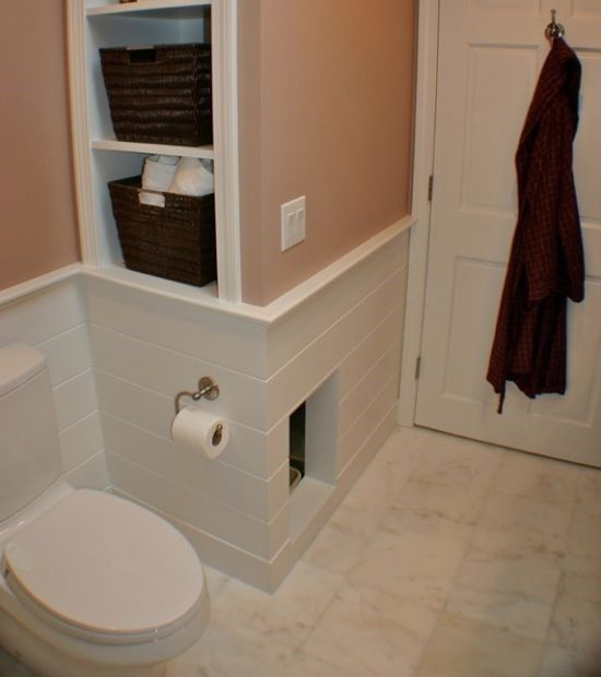 a built-in cat toilet unit in the powder room, with an entrance and clad with tiles to perfectly match the house