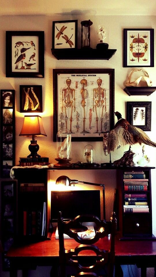 a chic Gothic home office with a desk with additional bookshelves, a vintage poster gallery wall, a heavy carved chair and a vintage table lamp