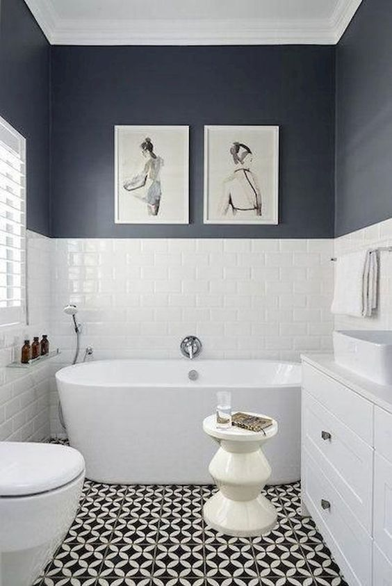 a chic black and white bathroom with a mosaic floor, black and white walls, a tub and a white vanity
