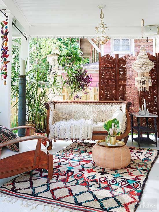 a chic boho porch with a wood carved bench, a chair, a printed rug, lanterns and a carved wooden screen