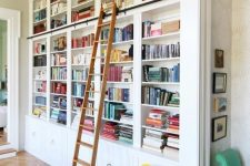 a chic built-in bookshelf unit with a ladder, a mustard chair and additional lights is very chic