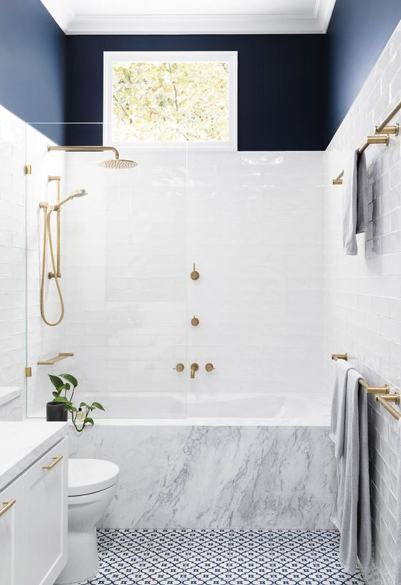 a chic contemporary bathroom with a mosaic floor, a marble clad tub, a navy toouch and gilded hardware