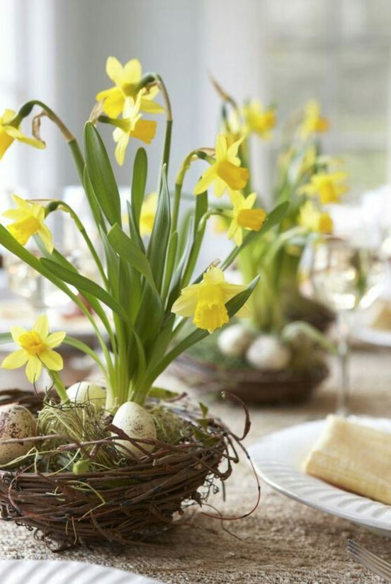a chic spring centerpiece of a fake nest with eggs, moss and daffodils is an amazing idea for any table