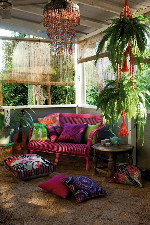 a colorful screened boho porch with a pink loveseat, colorful printed pillows, potted plants and a colorful glass chandelier