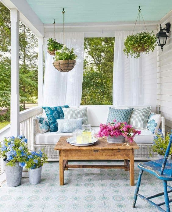 a colorful spring porch with potted greenery and blooms, printed pillows and vintage furniture