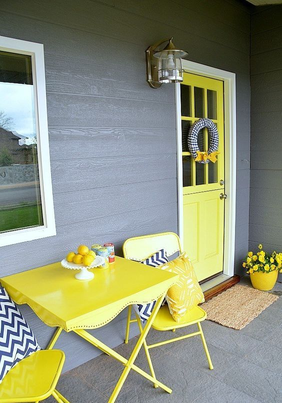 a colorful spring porch with yellow furniture, door and a pot plus blooms and chevron pillows