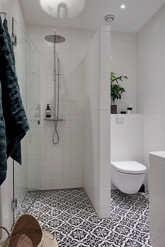 a contemporary bathroom with mosaic tiles, white tiles on the walls, potted greenery and a basket for storage