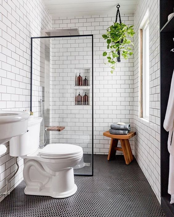 a contemporary bathroom with penny and subway tiles, built-in shelves, a sink and a wooden stool