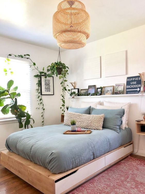 a contemporary small bedroom with a storage bed, a ledge with a gallery wall, a wicker lamp and potted greenery