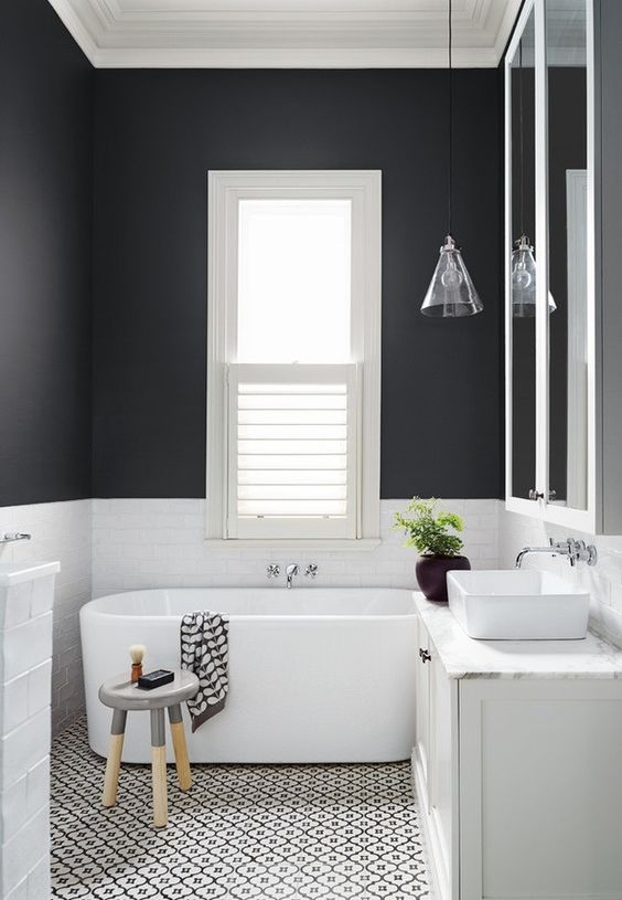 a contrasting bathroom with black and white walls, a mosaic floor, an oval tub, a stool and a glass cone pendant lamp