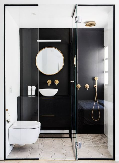 a contrasting small bathroom with a black statement wall and vanity, a shower, a round mirror and a bowl