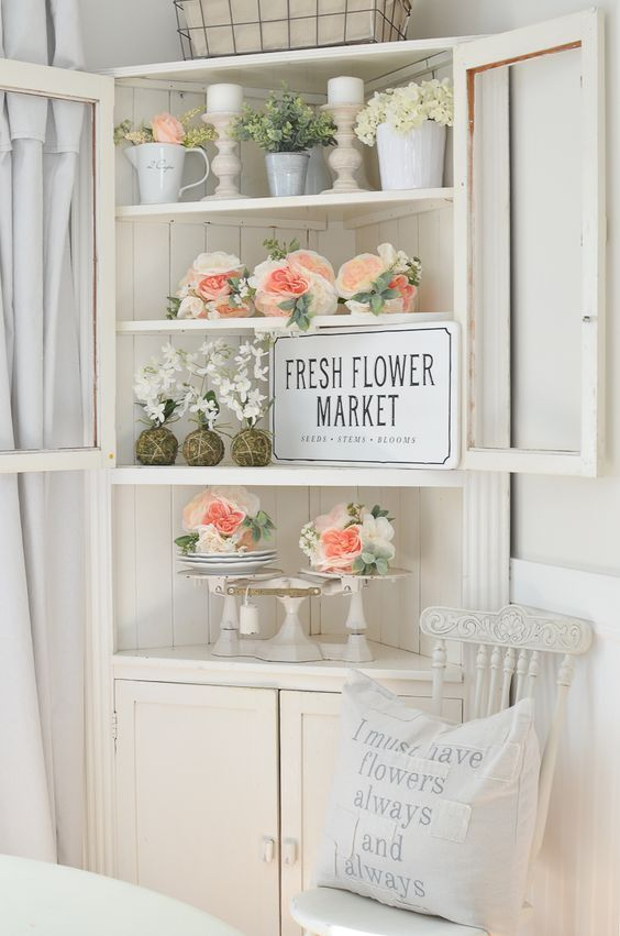 a corner bureau with fresh peachy and white blooms, candles, vine balls and an artwork