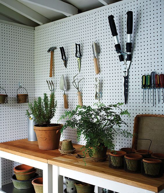 a couple of tables with shelves underneath and pegboard walls around are a contemporary option for storing everything in your shed