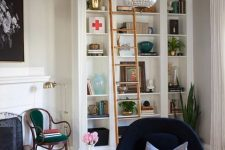 a cozy and stylish reading nook with built-in bookshelves, a navy chair with a footrest and a refined chair