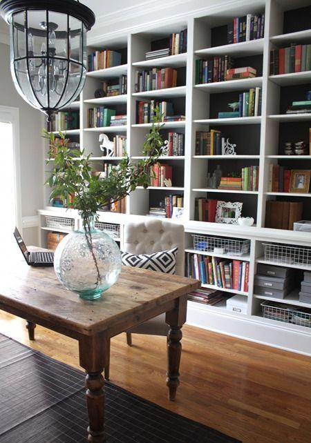 a dark built-in bookshelf with lots of books, wire baskets, greenery, figurines and other decor