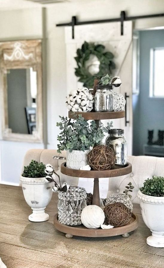 a farmhouse kitchen stand with cotton, greenery in pots, vine balls and silver jars