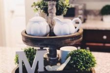 a farmhouse kitchen stand with greenery, letters, an artwork, porcelain and mugs for spring
