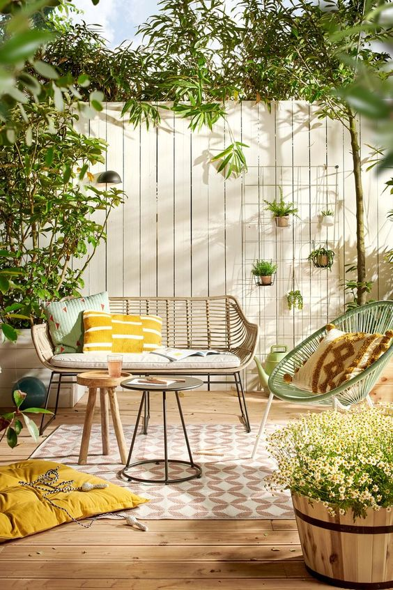 a fresh and welcoming spring terrace with wicker furniture, potted greenery and blooms and touches of mustard and green