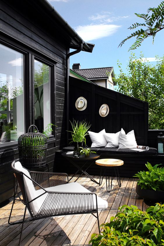 a fresh spring Scandinavian terrace in black and white, with potted greenery and greenery in cages