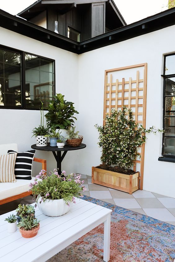 a fresh spring modern terrace with potted blooms and greenery, simple wooden furniture and printed pillows