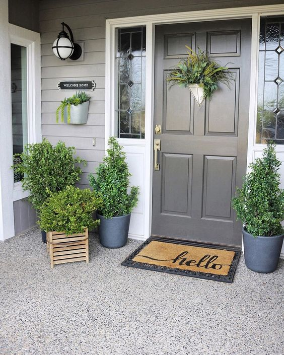 a fresh spring porch decorated only with greeneyr in pots and crates and with greenery on the door