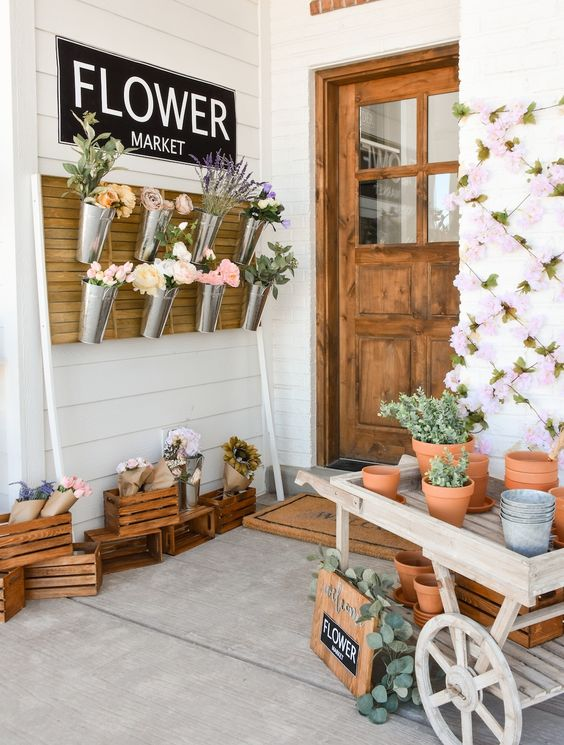 a fun idea to turn your porch into a flower market hanging blooms in buckets and placing them everywhere